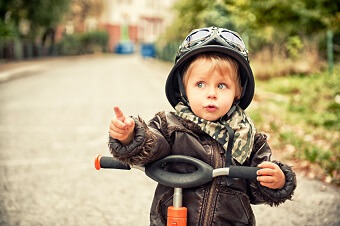 a little boy pointing while sitting on his bike