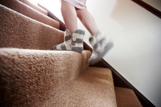 Woman in nightgown and slippers walking upstairs