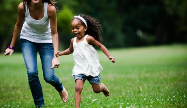 white gilr in her 20's playing in the park, with an african american little girl. colorfull, high contrast images,
