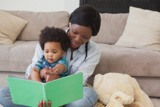 Afro mother with cute baby reading story book in the living room at home