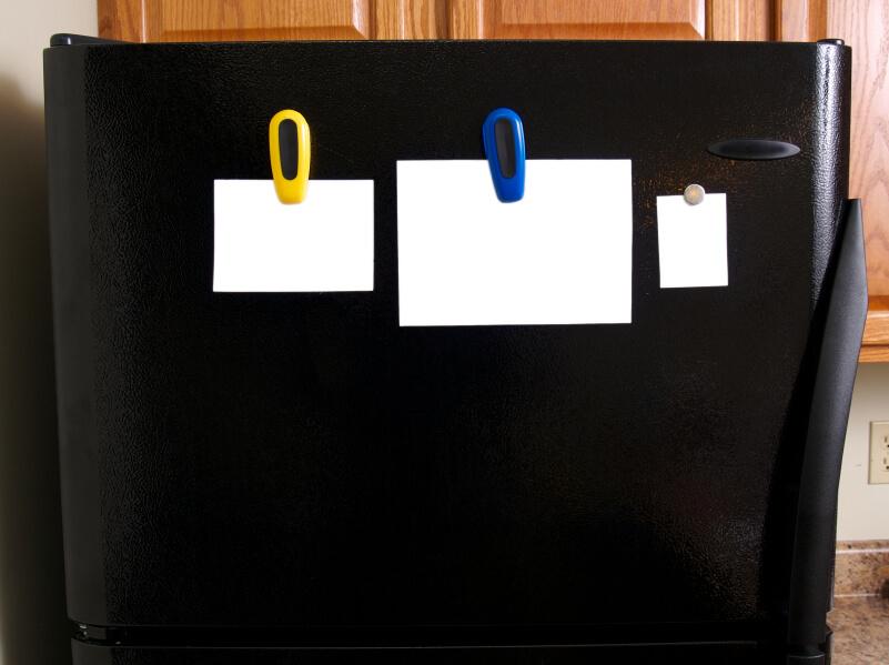 some white notes handing on a fridge