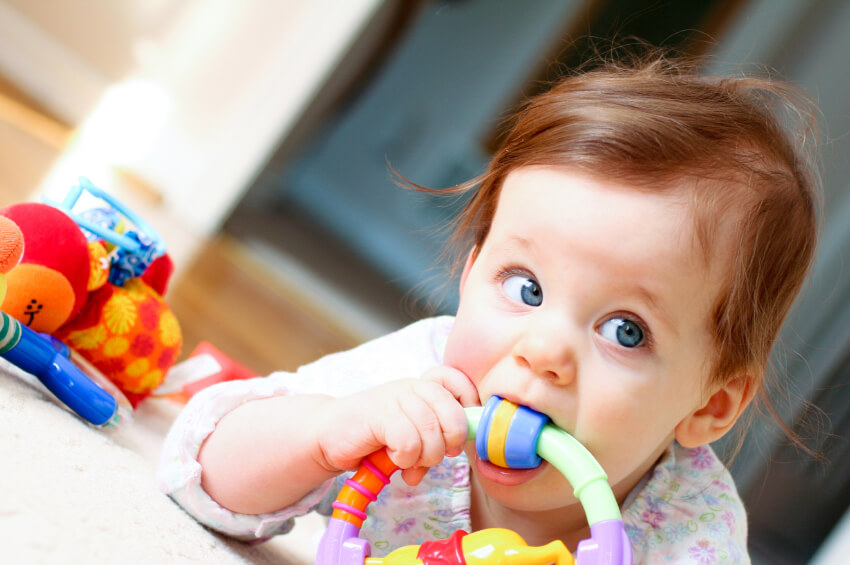 a young girl chewing on some toys