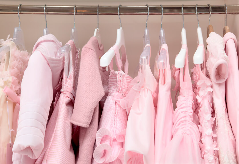 a line of pink clothes in a closet