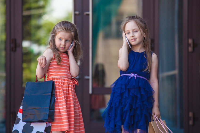 two young girls using mobile phones while shopping