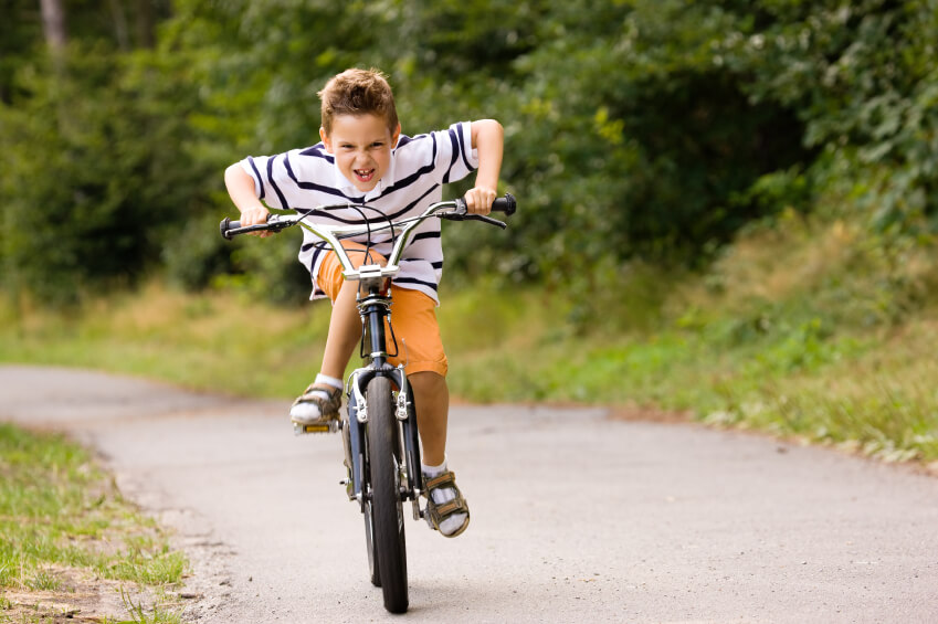 a young boy riding his bike fast
