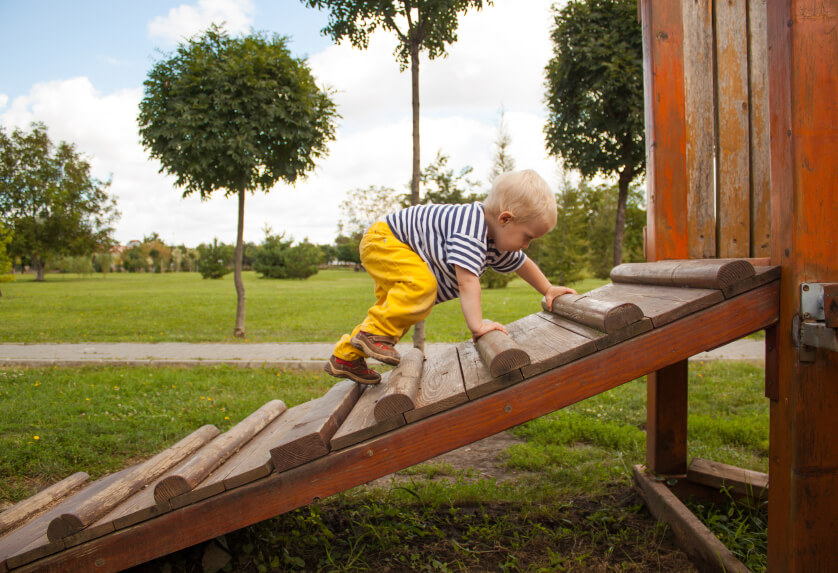 a young boy climbing playground equipment