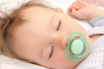 a baby sleeping with a pacifier in their mouth