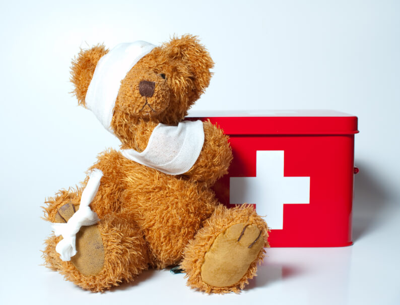 a stuffed toy bear wearing bandages in front of a first aid kit