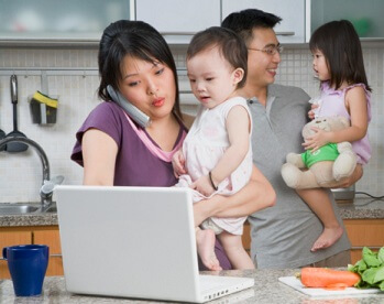 a young family in the kitchen looking very busy
