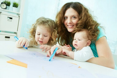 a mom smiling while her kids are drawing