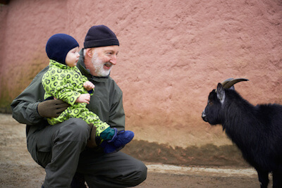 a dad and his son looking at a goat