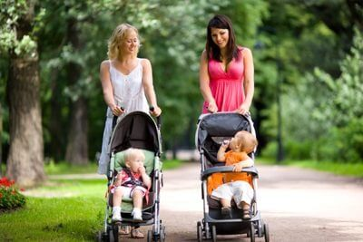 two moms walking their baby's in their strollers