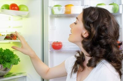 a woman looking into a fridge