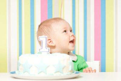 a baby boy in front his first birthday cake