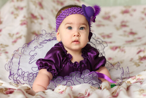 a baby dressed in a purple outfit