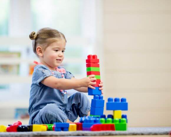 a young girl playing with building blocks