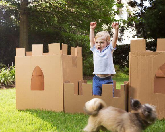 a young boy playing with a cardboard castle outside