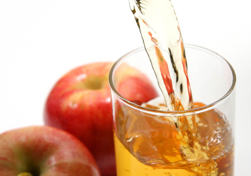 a person pouring a glass of apple juice