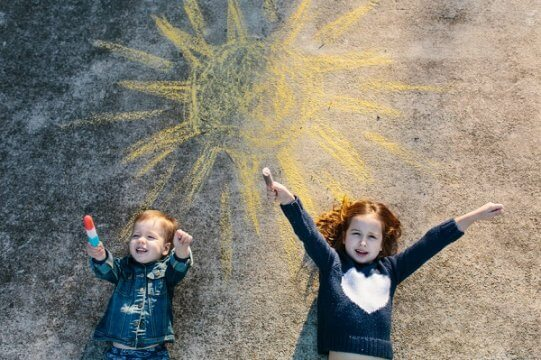 two girls lying on concrete ground with a sun drawn in chalk