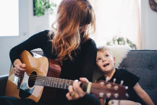 A candid portrait of a mother playing guitar and her son singing along
