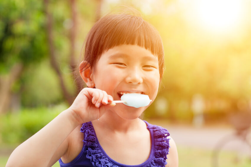 a young girl eating an ice pop