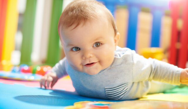 A young baby boy plays in his brightly coloured playpen. He is on his tummy discovering how to move and playing with his toys. He has a cheeky smile on his face.