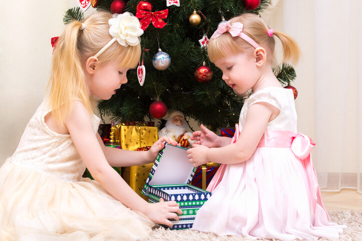 two young girls opening Christmas presents