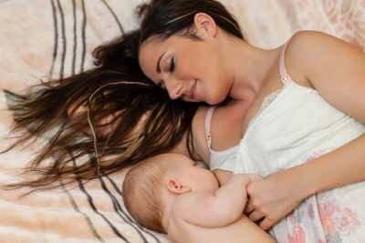 a mom breastfeeding her baby on the bed