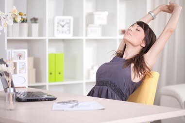a woman stretching while sitting in front of her laptop