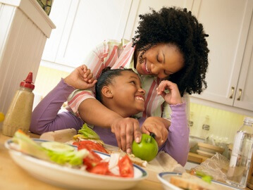 a mom making a snack with her daughter