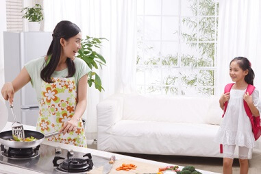 a mom cooking while greeting her daughter