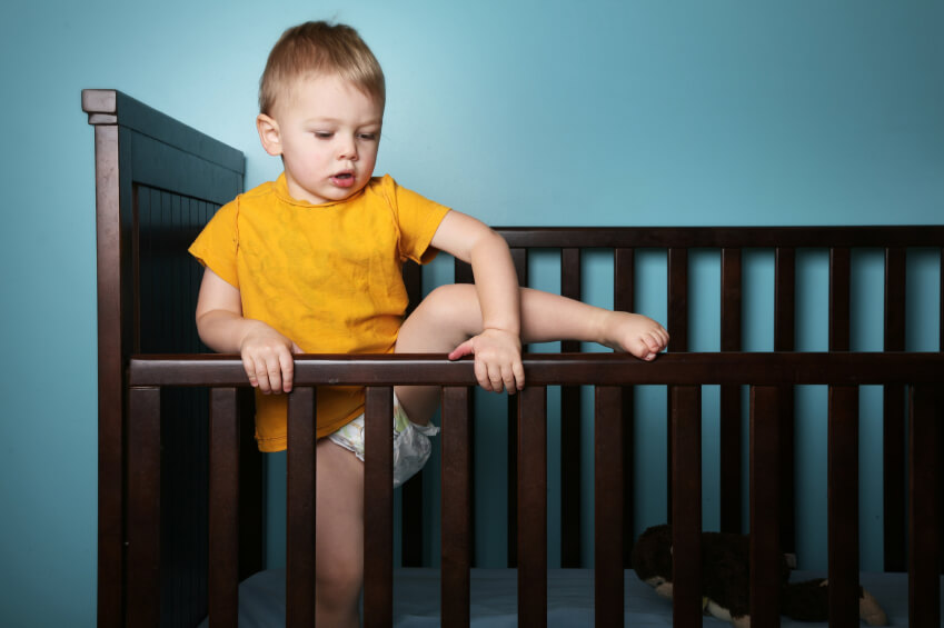 a young boy climbing out of his crib
