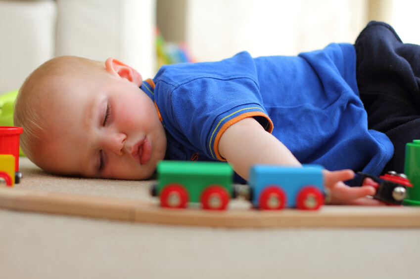 a young boy sleeping with his toys
