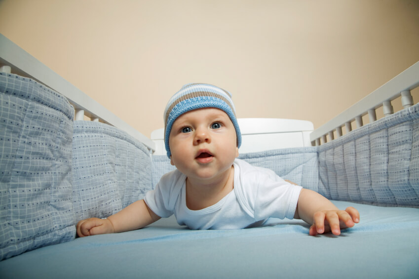 a young boy lying in his crib with bumpers