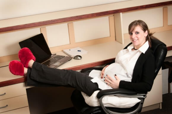 a pregnant woman smiling while sitting in a chair