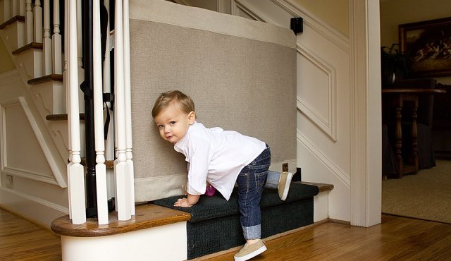 a boy being blocked from climbing the stairs by the stair barrier