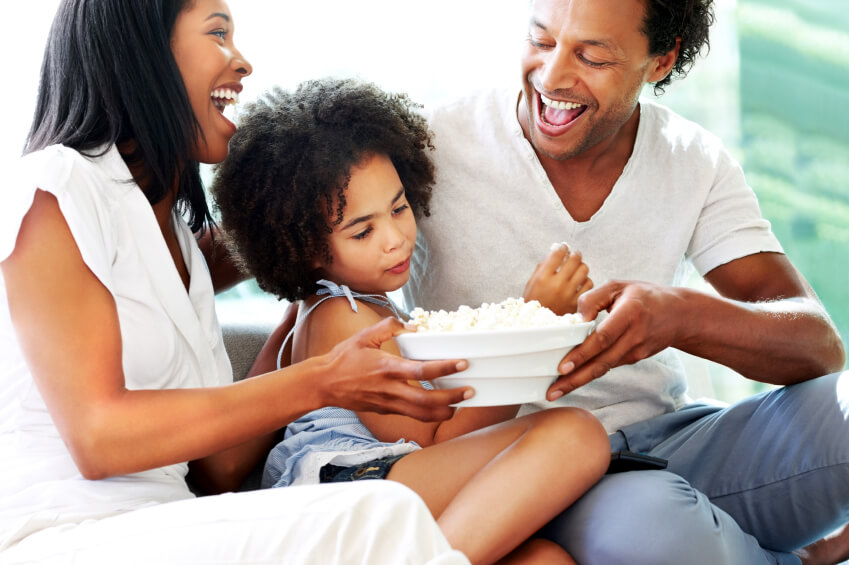 a family eating popcorn while watching a film