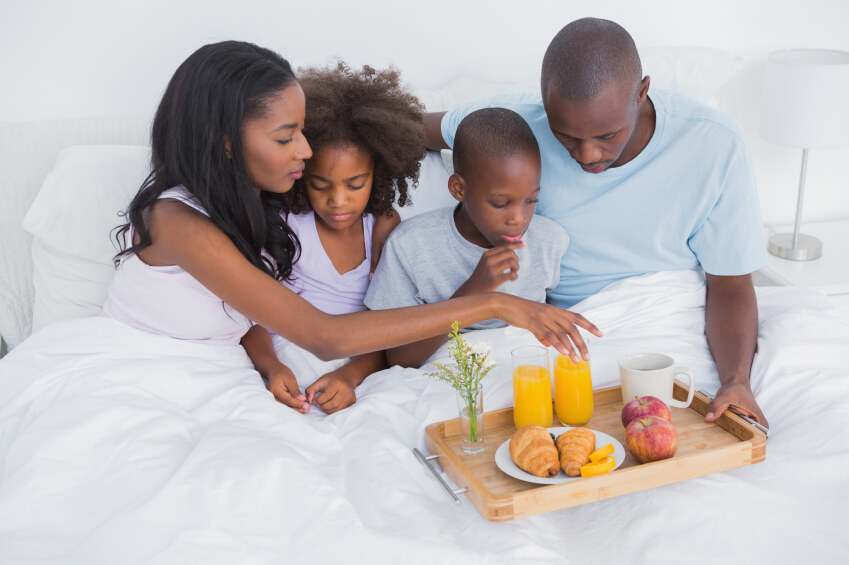 a family having breakfast in bed