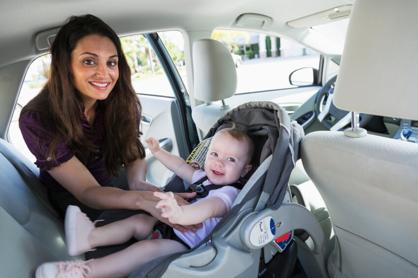 a mom putting her baby in a car seat