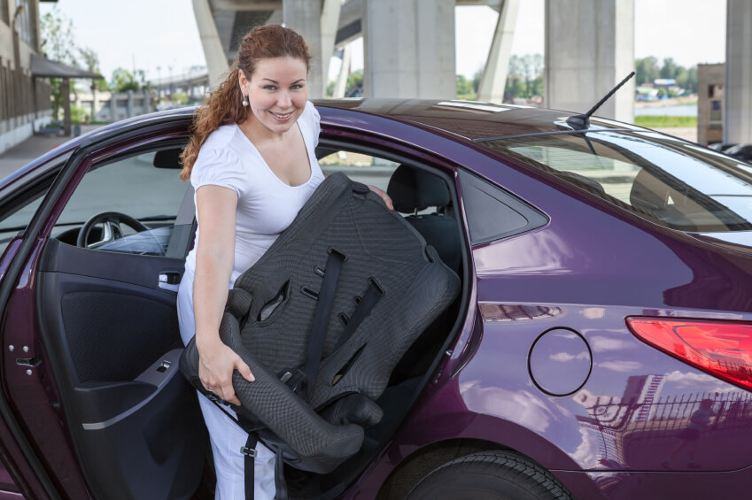 a mom taking out a car seat from the car