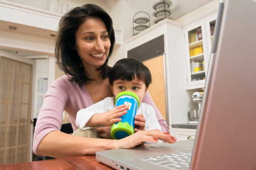 a woman holding her child while using a laptop