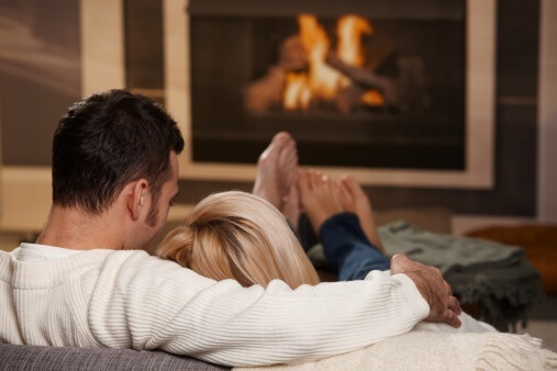 a couple sitting in front of a fire together