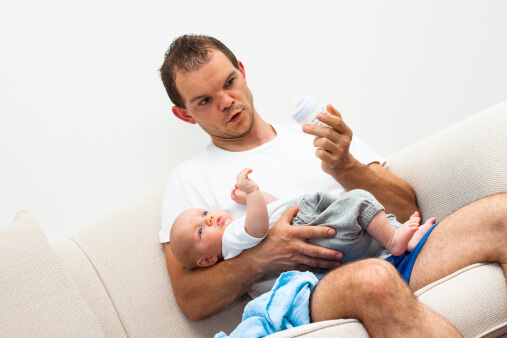 a dad holding his baby while looking at a feeding bottle