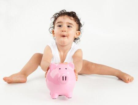 a baby holding a piggy bank