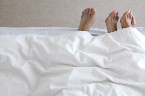 two people's feet poking out of bedsheets