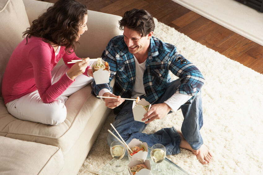 a couple at home eating takeaway food