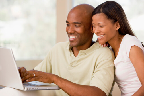 a couple looking at a laptop together