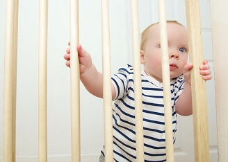 a baby standing behind baby gates