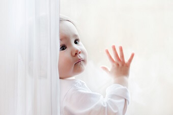 a baby leaning against a window