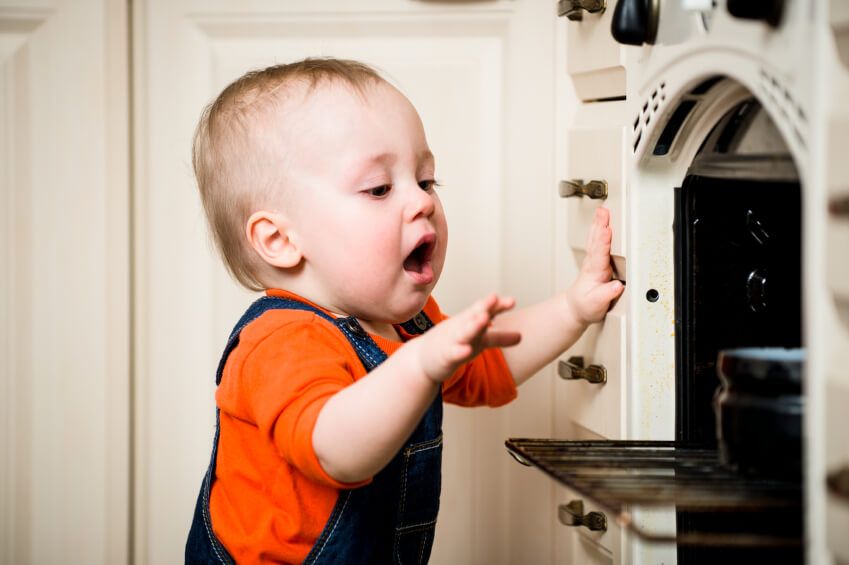 a baby reaching into an oven
